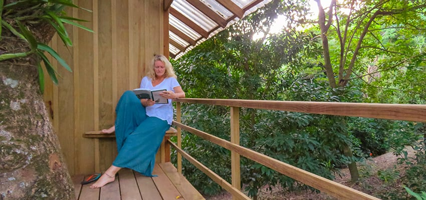 Sitting outside the treehouse at Roland Rumm's Garden Guesthouse reading