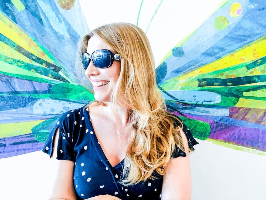 Abigail King from Inside the Travel Lab sitting wearing her sunglasses in front of painted colourful wings