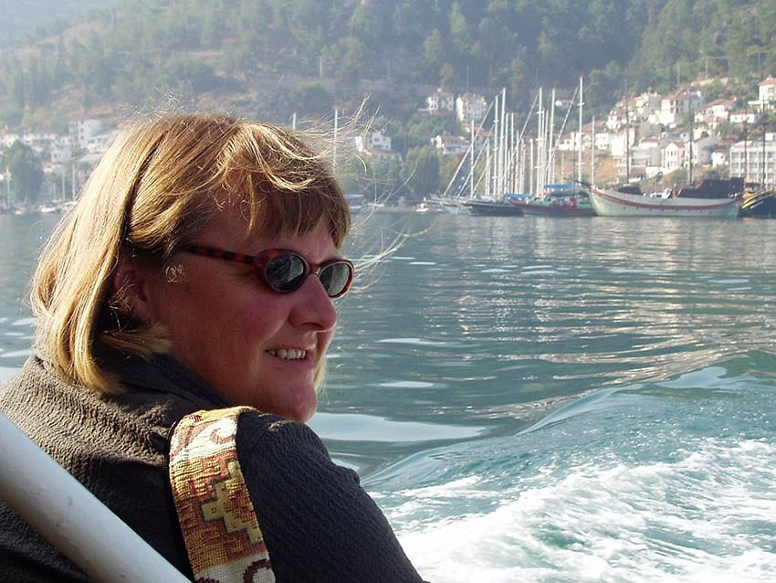 Andrea from Happy Days Travel Blog in Turkey wearing sunglasses with water and yachts in the background