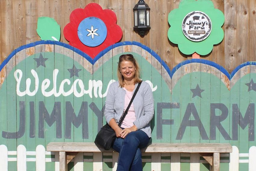 Sally from The Foodie Travel Guide sitting in front of a Welcome to Jimmy's Farm sign wearing a lavender cardigan and jeans