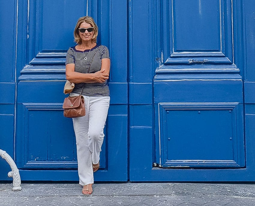 Suzanne Jones - The Travelbunny standing outside blue doors wearing a striped top and grey trousers