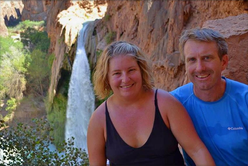 Jenn in a black strappy vest top and Ed in blue t-shirt  from Coleman Concierge with Hualapai Hilltop and waterfall in the background