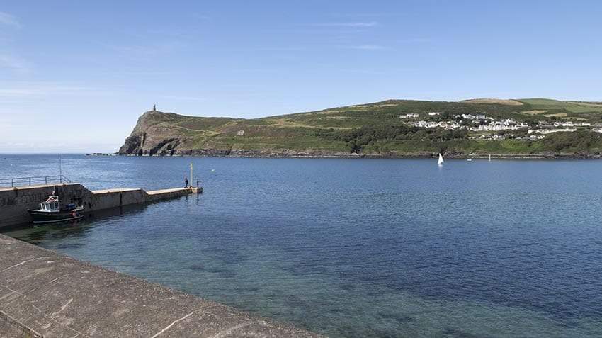 A beautiful day in Port Erin, Isle of Man with the blue sea and great hill in the background