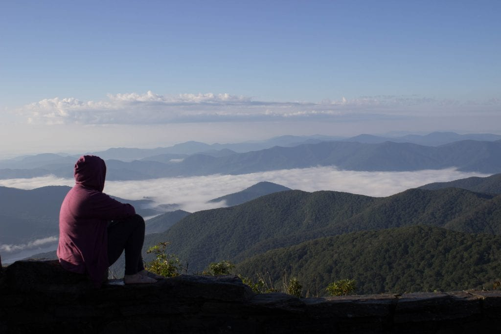 Woman in a purple hoodie with hood up looking out over fog covered hills