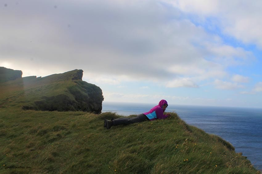 Woman wearing a pink and blue hoodie lying on a grass cliff looking out over the sea