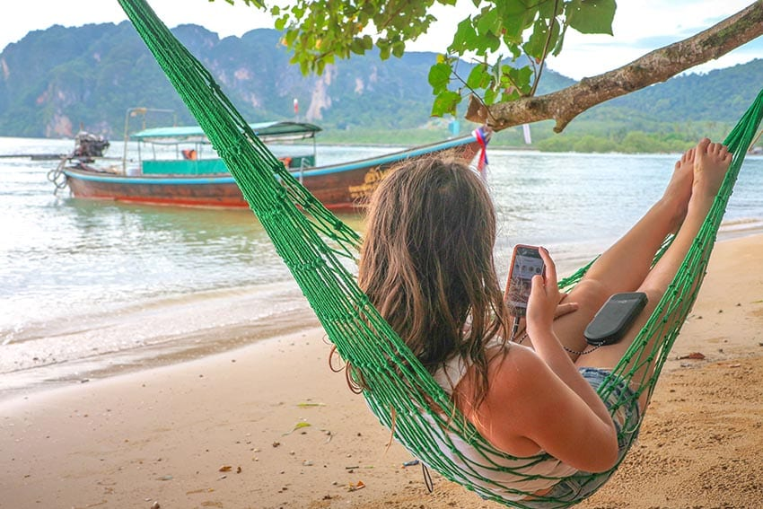 Girl sitting in a green hammock with her back to the camera looking at her mobile phone with a Thai boat in the background on the sea