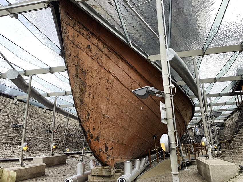 The iron hull of the SS Great Britain in dry dock underneath a glass plate with struts holding it up