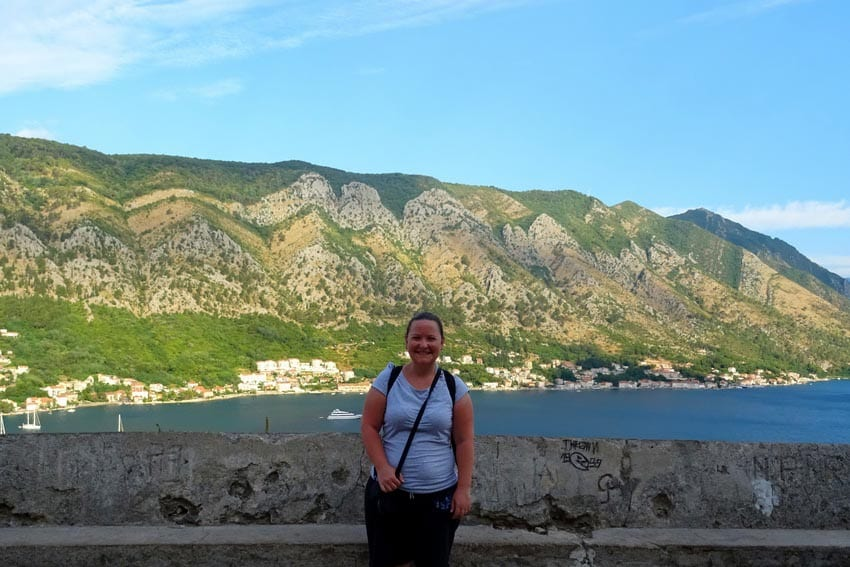 Woman wearing a pale blue t-shirt standing in front of a wall with blue water and green hills behind