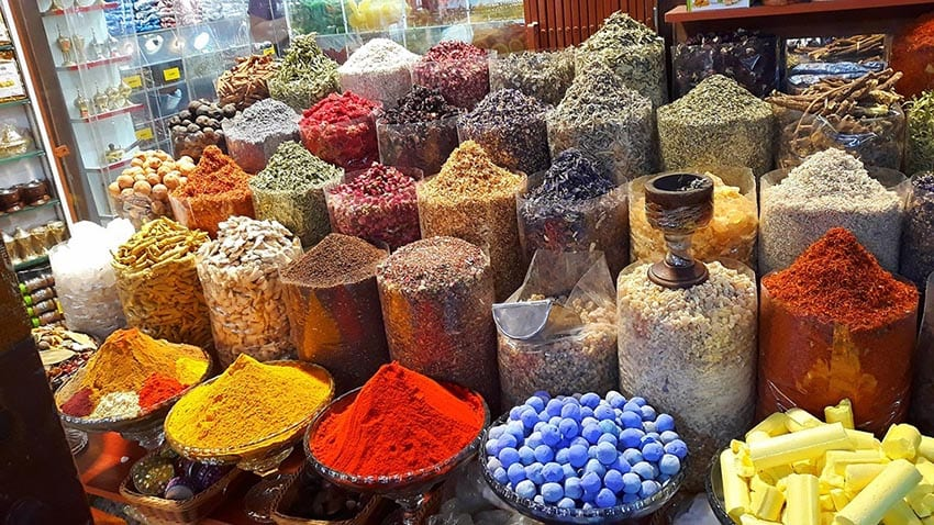 Jars and dishes of different spice with yellow, gold and red at the front, a must on your 7 day Dubai Itinerary