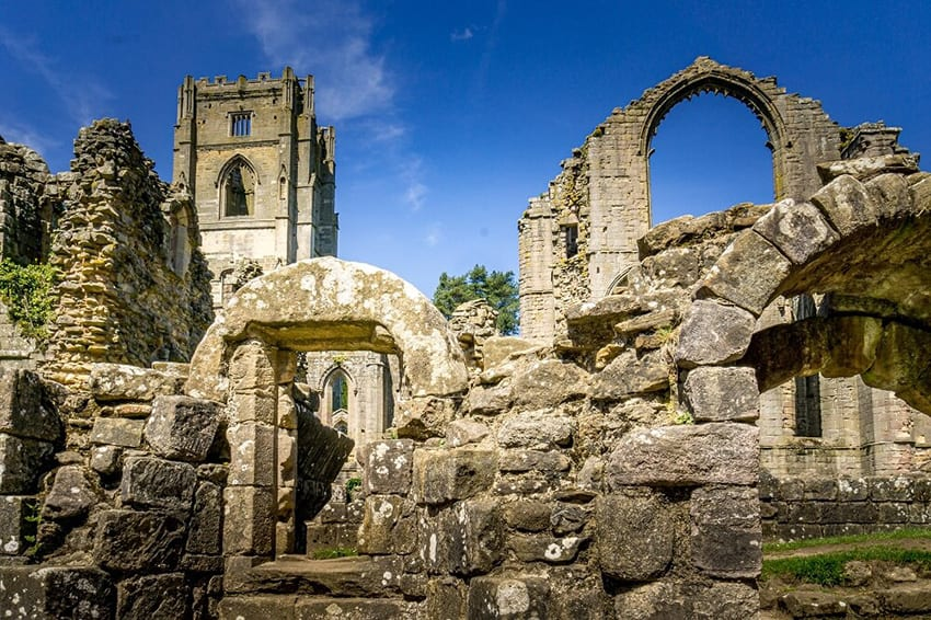 Ruins of Fountains Abbey, with arch to the right and bell tower to the left