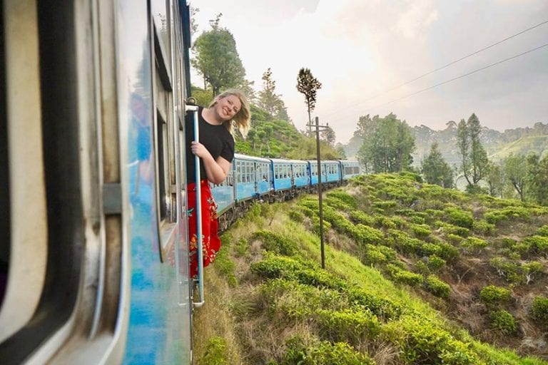 Leanne wearing a black top and red skirt leaning out of the blue train from Horton to Ella in Sri Lanka looking over the lush green landscape