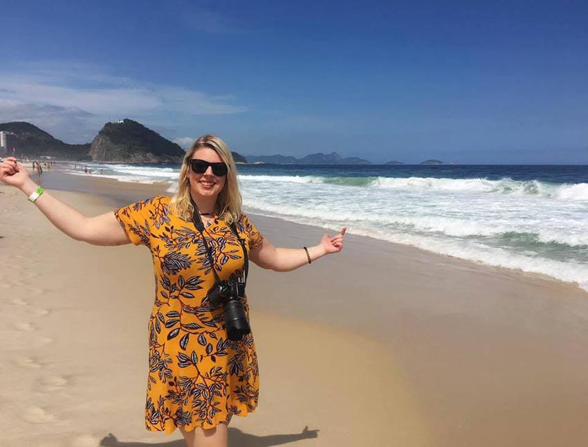 Leanne wearing a mustard patterned dress and sunglasses on a beach with blue skies behind