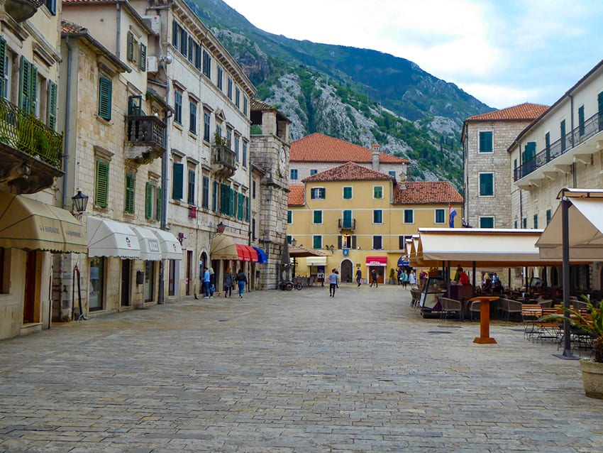 Old Town Kotor showing a cobbled street restaurants with awnings on the right and shops with awnings on the left. A yellow building in the distance with hills behind.