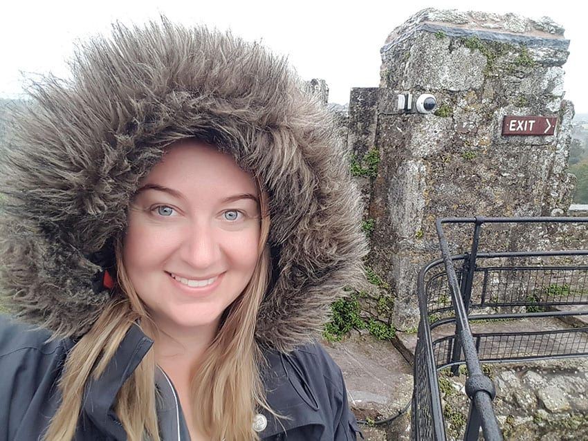 Roma with a furry hood photographed just before kissing the Blarney stone in Ireland with the stone castle walls in the background