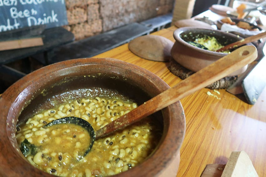round clay pots with bean curry in with wooden ladle sitting on a wood bench other pots in the background