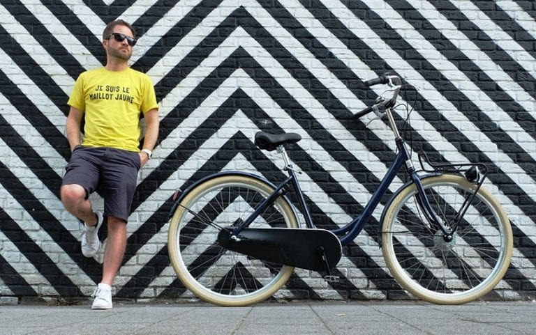 """Steve wearing a yellow t-shirt which says """"Je suis le maillot jaune"""" (translation: I am the yellow jersey) standing with his back against a wall with black and white diagonal stripes next to a bicycle in Rotterdam"""