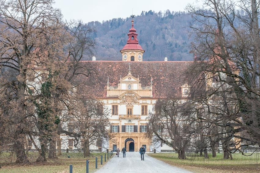 Graz show an avenue flanked by trees in winter leading to a large building with a bell tower