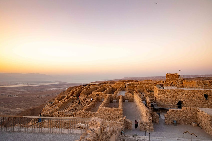 the ruins of Masada Fortress with the sun rising in the background. The walls show the rectangular layout of the rooms in the fort.