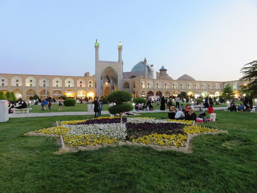 Naqs-e Jahan Square with arched sand coloured buildings in the background with three domes on the right and a larger arched entrance in the middle. In the foreground is a grassy area with a seven sided star planted with white, purple and yellow flowers and a tree in the middle. People are sitting on the grass or walking in the grounds.