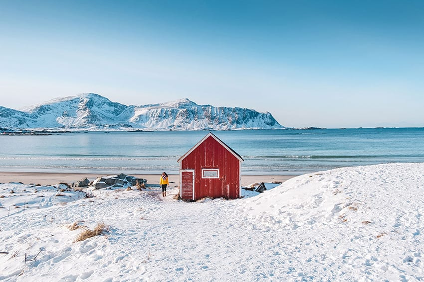 Michele in yellow jacket standing next to a red house with  blue sea and snowy mountains behind and snow in the foreground