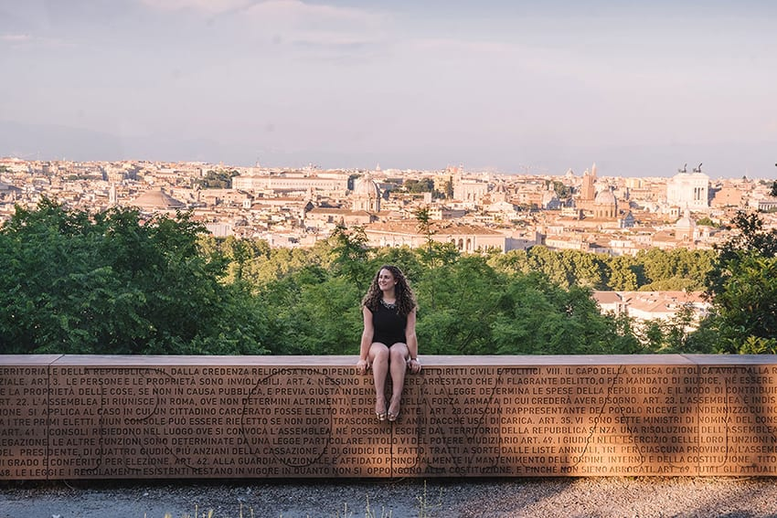 Michele in black dress sitting on a wall with Rome carved into it with the Italian city of Rome in the background