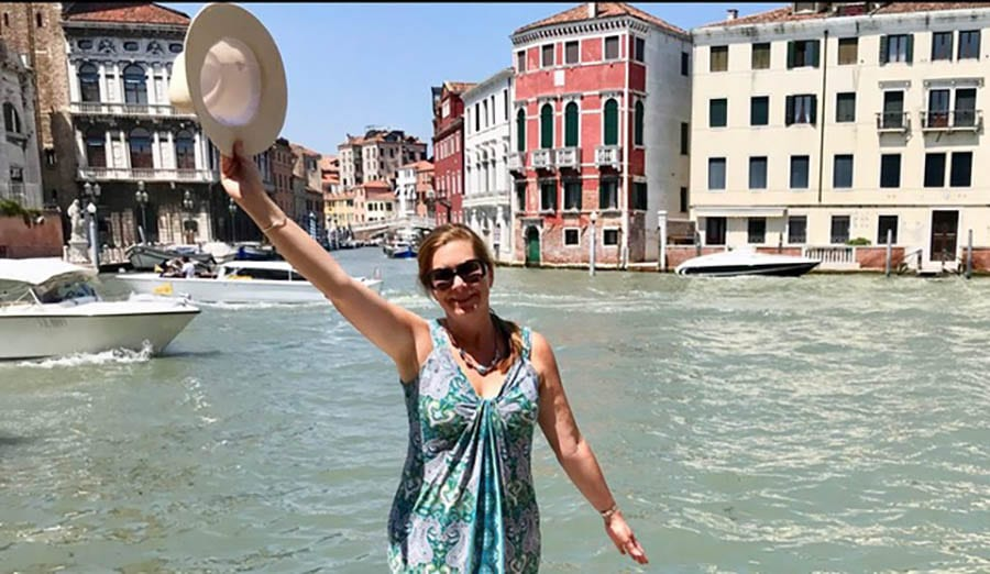 Angie from Where Angie Wanders in short sleeved dress wearing sunglasses and with a hat in her raised hand. In the background in the canals of Venice and four-storey buildings in cream and pink