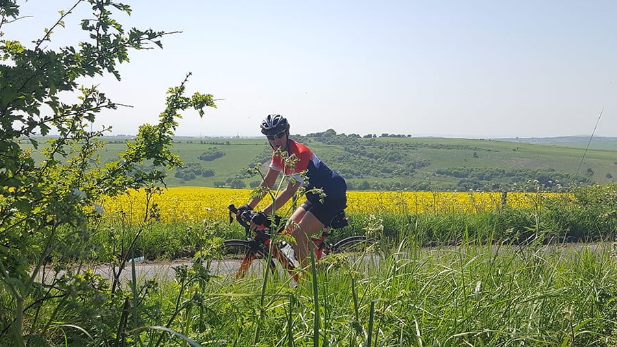 lady on bicycle wearing a crash helmet and cycling on a road through green fields and yellow rape fields