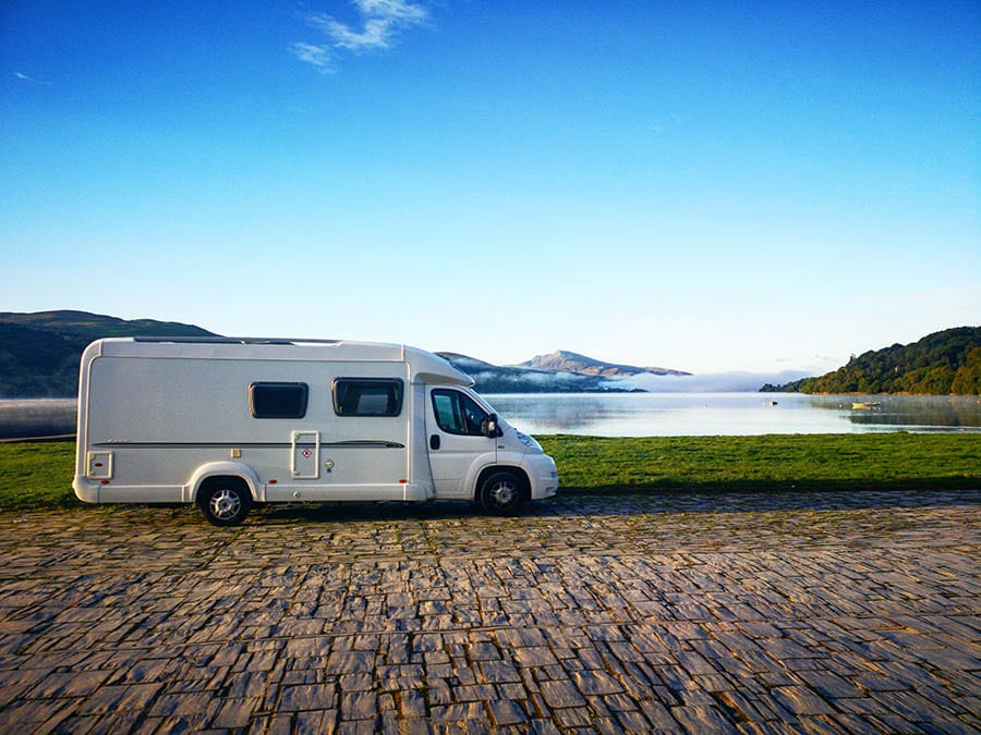 White camper van sitting next to green grass with lake and hills in the background
