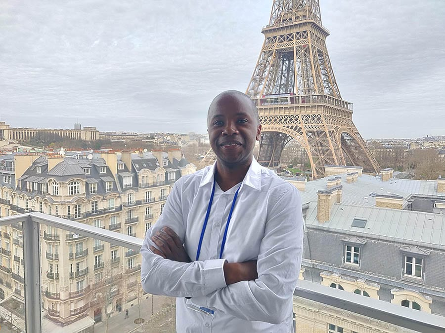 Roobens, a black travel blogger, wearing a white shirt and blue lanyard standing on a balcony with his arms crossed. he is smiling and has the Parisian rooftops in the background and the base of the Eiffel Tower
