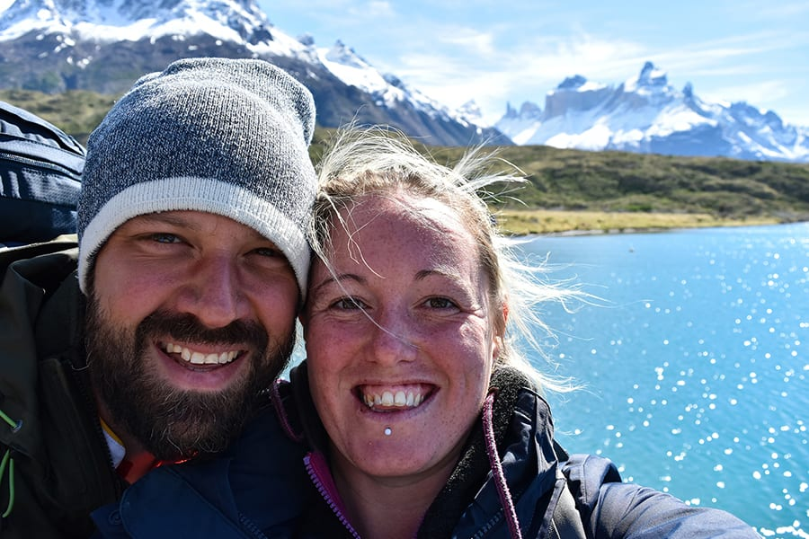 A smiling couple. the man with a dark beard and moustache and a grey beanie with white rim and a girl with blonde hair in front of a blue lake with snowcapped mountains in the background