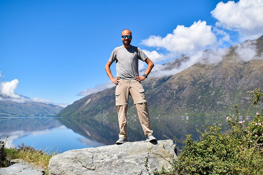 Man wearing blue tinted sunglassed, grey tshirt and beige cargo trousers standing on top of a rock. In the background the mountains and clouds are reflected in a lake