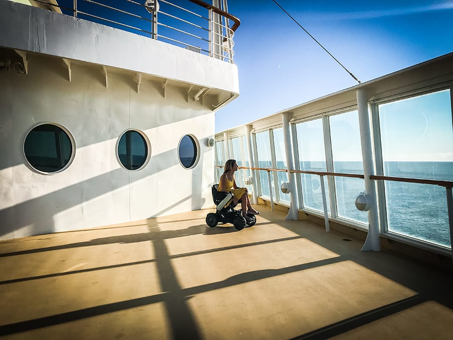 Sylvia from Spin the Globe in a wheelchair on board a cruise ship deck looking out through the glass walls towards the sea
