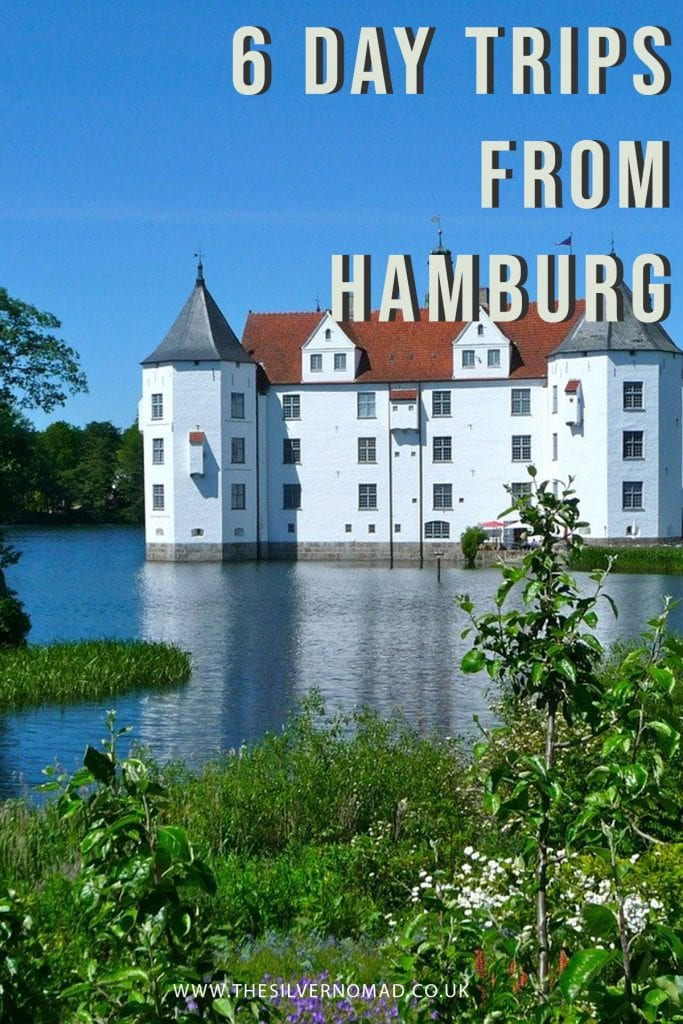 image of a white castle surrounded by a blue lake with the words 6 day trips from Hamburg superimposed