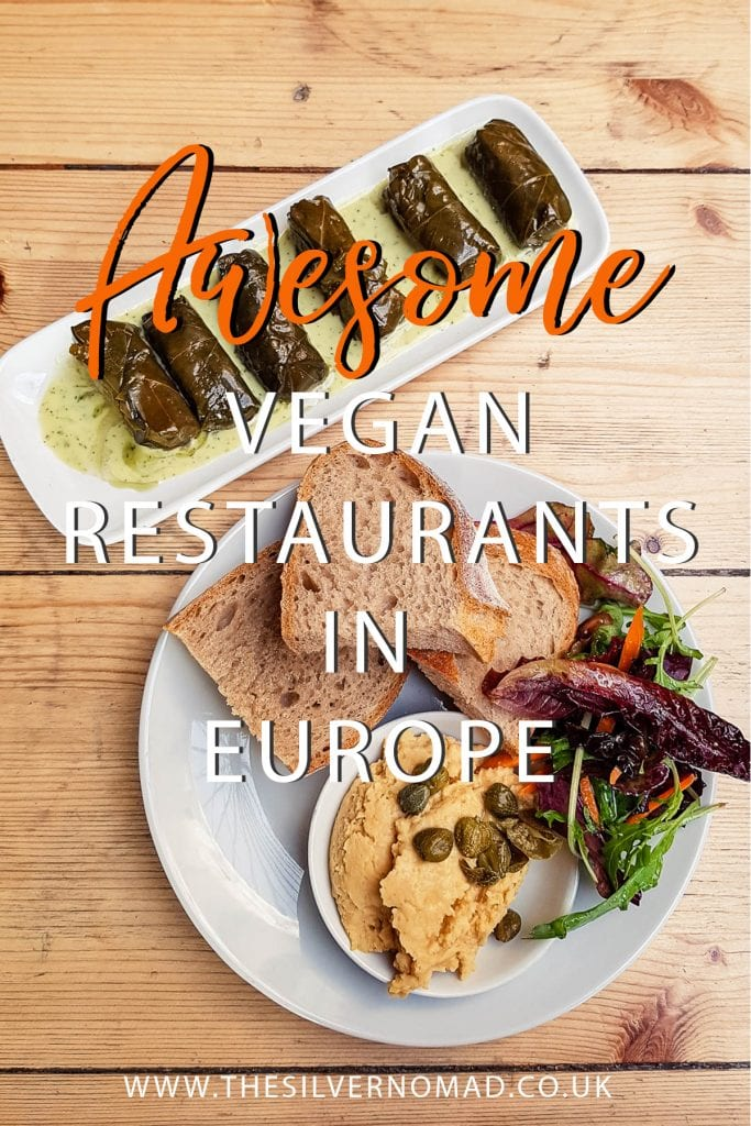 "Dishes of vegan food including wrapped vine leaves on a slim white rectangular dish and salad, bread on a white round plate with humous in a white bowl. Writing ""Awesome vegan restaurants in Europe"" superimposed on top"