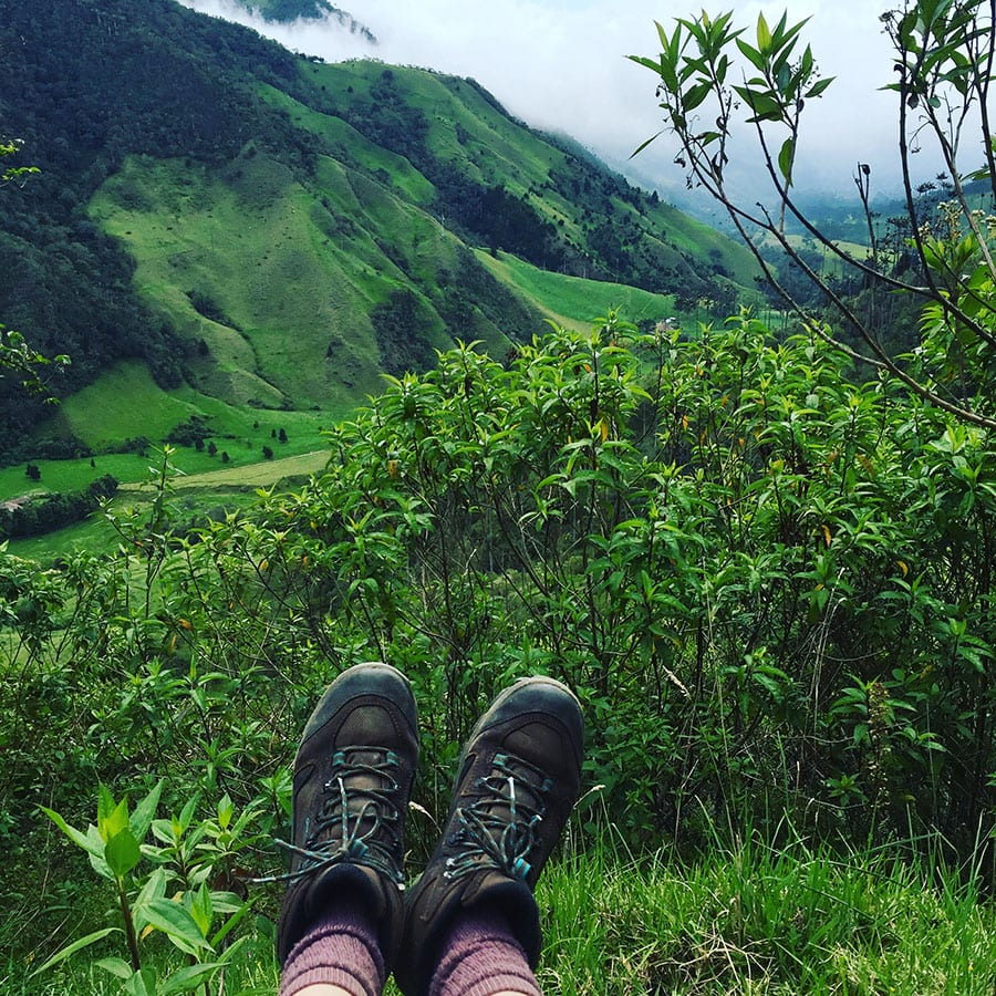 pair of boots against a background of lush green hills