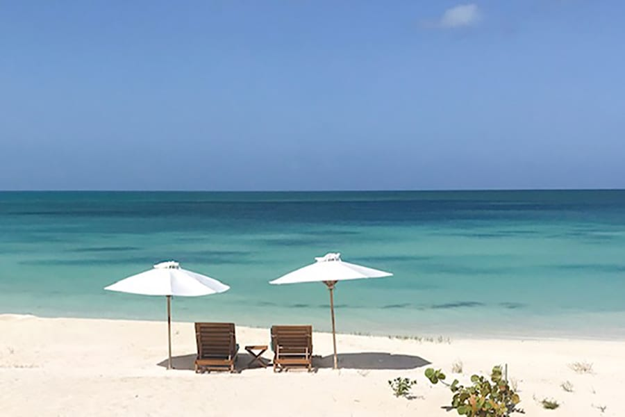 two sun loungers under white parasols on a white and pink sand beach next to the turquoise and blue sea with a clear blue sky above