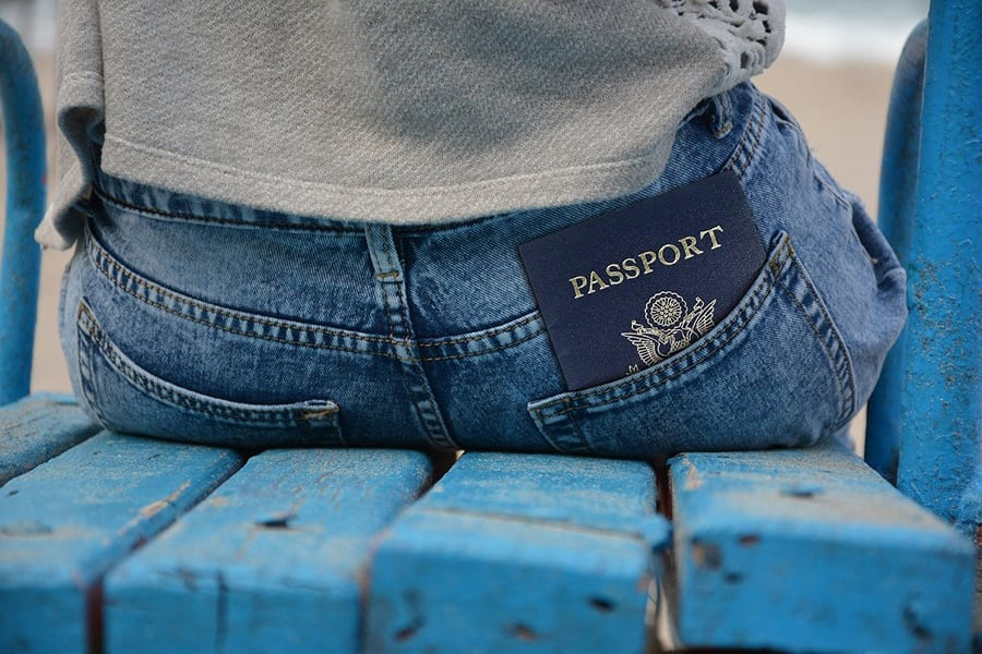 image of the back of a woman wearing blue jeans and a grey sweatshirt sitting on a blue wooden seat with a blue passport in her jeans pocket