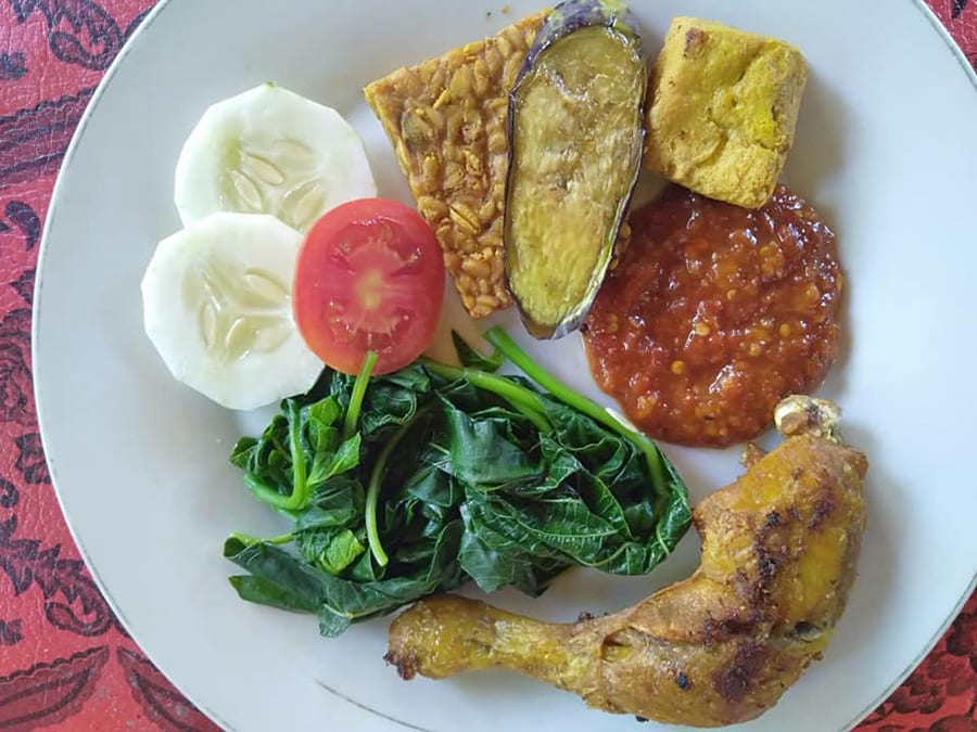 White plate on red tablecloth with fried chicken leg, greens, sliced tomato and cucumber, tempe, fried aubergine, corn fritter and tomato sambal