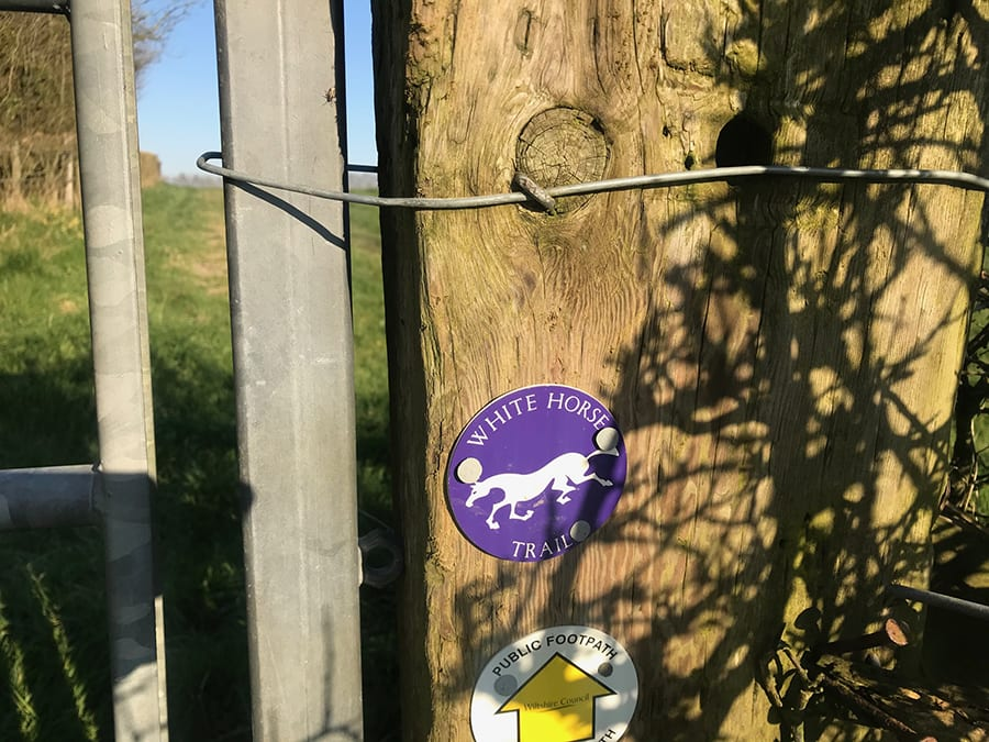 purple disk with White Horse Trail writing in white and and a white horse above a white Public Footpath disk with yellow up arrow saying Wiltshire Council