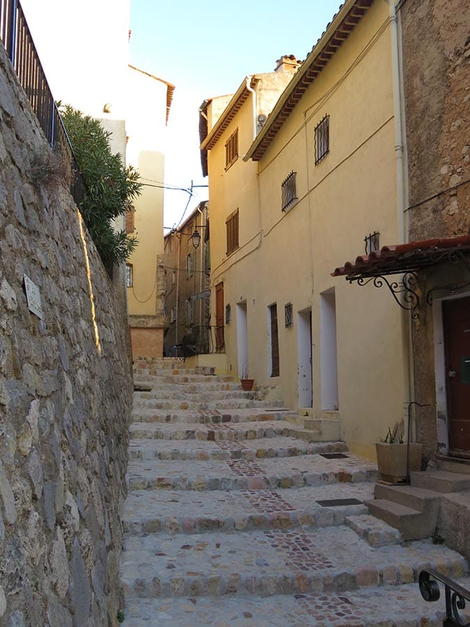steps up between a wall on the left and a yellow building on the right in Callas