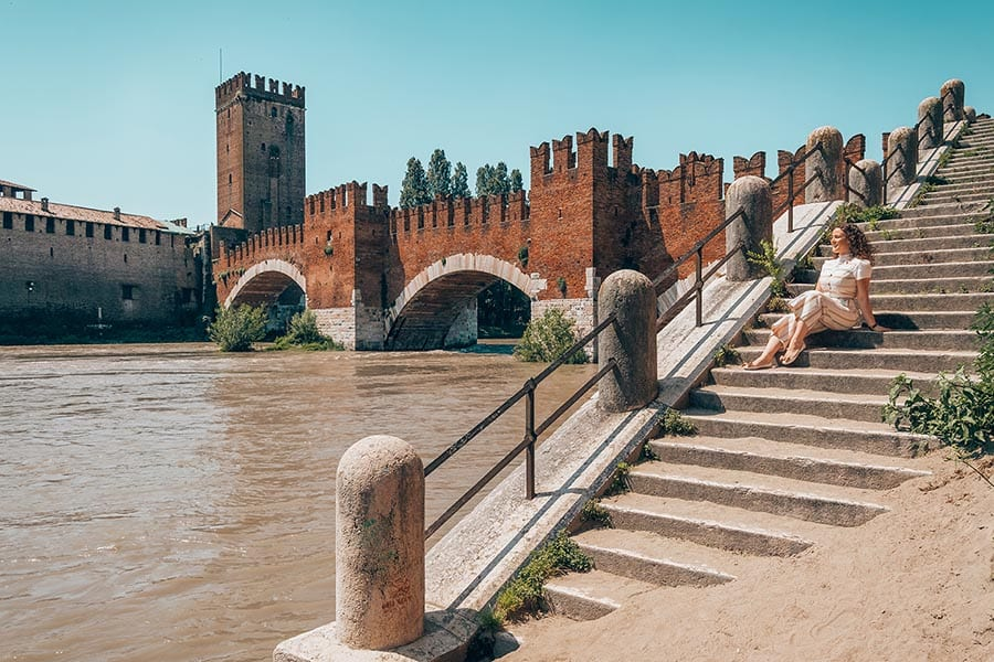 smiling woman sitting on steps with Verona Castle in red brick with arches to her left
