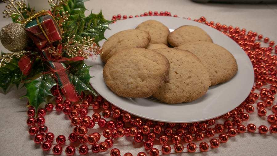 white plate with round biscuits surrounded by red shiny beads and holly with a tartan bow.