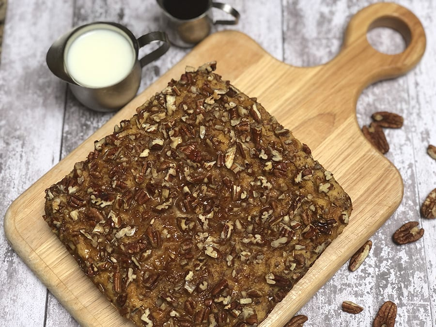 wooden board with square of brown french toast covered in pecans with pecans around - Chef Denise's Favourite Christmas bake for Breakfast