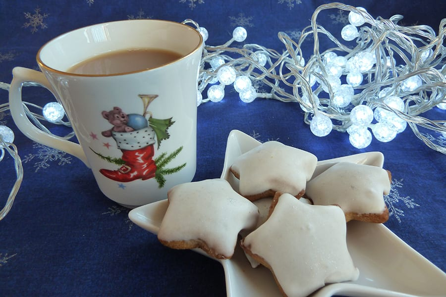 tradition star shaped Lebkuchen biscuits with icing sugar topping next to a cup of tea in a mug with a red Christmas boot on it and toys coming out the top all sitting on a blue fabric with silver snowflakes and lit by some white fairy lights