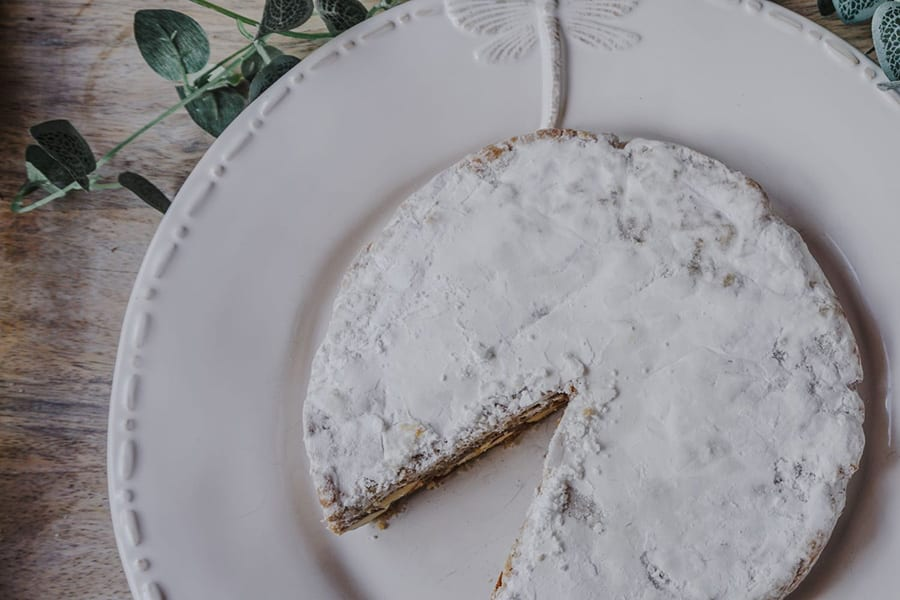 round cake topped with icing sugar sitting on a round white plate with raised dragonfly motif. In the background is some ivy.