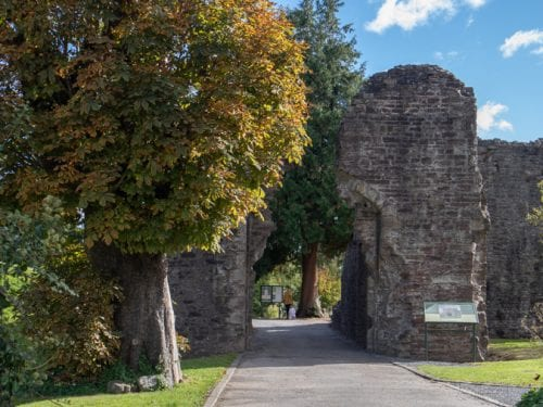 ruins at the entrance of Abergavenny Castle with trees on the left and grass and plants on the right