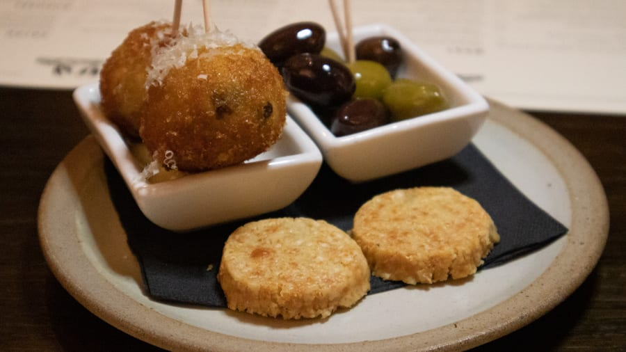 Two arancini balls, green and black olives and parmesan crisps on a black napkin on a stone coloured plate
