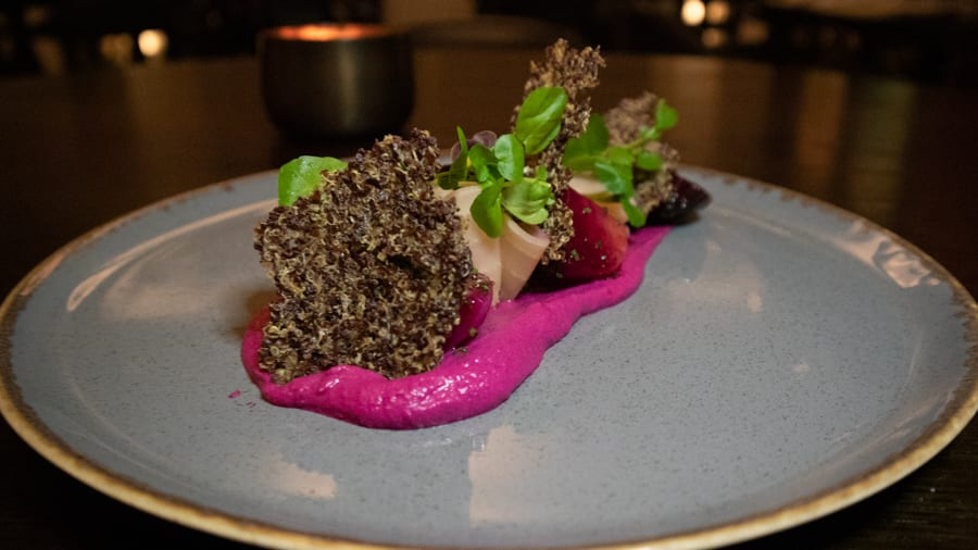 blue plate with bright pink beetroot hummus topped with rainbow beetroot, quinoa crisp and microgreens
