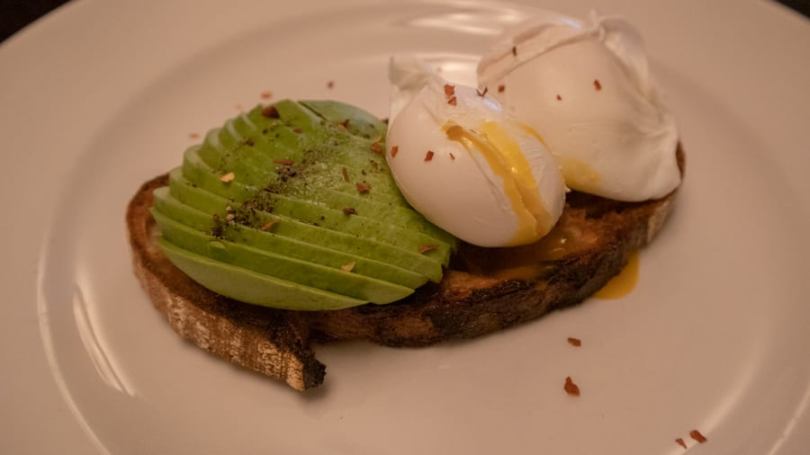 sourdough toast with sliced avocado and two poached eggs topped with pepper and chilli flakes. One of the eggs is split and the yellow yolk is oozing out