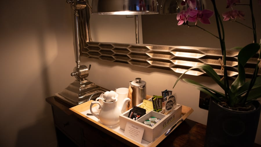 Tray with white teapot, silver cafetiere and a selection of tea sitting under a silver framed mirror and next to a pink orchid